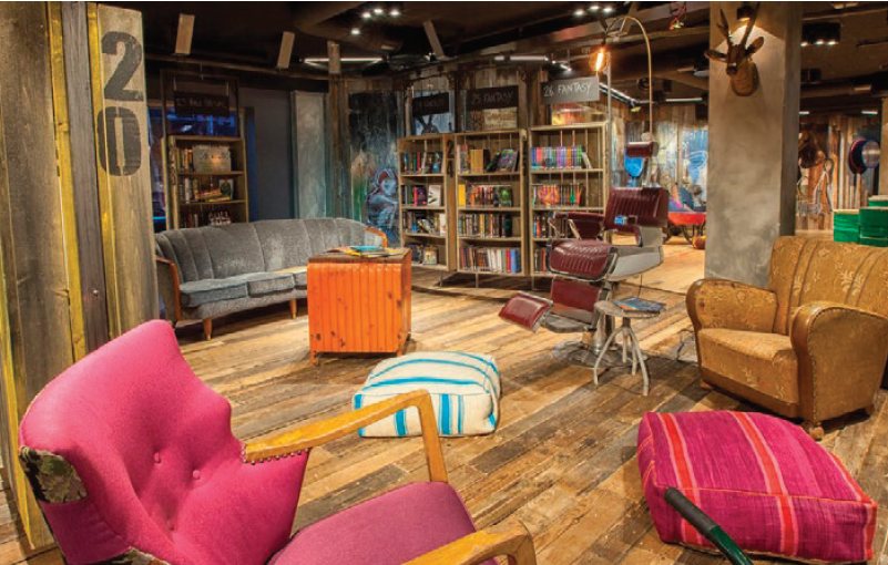 Rustic room with unfinished wood floors, bookshelves, floor cushions, a hot pink arm chiar, an antique barber chair, a large tan arm chair and a grey sofa