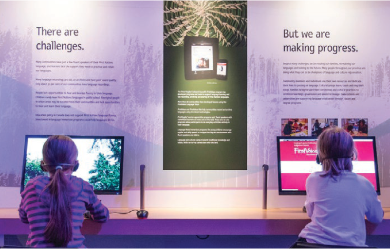 Two children sitting at interactive screens in the Our LIving Languages exhibit