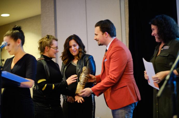 Executive Director, Ryn Hunt, awarding a BCMA Award winner an owl statue.