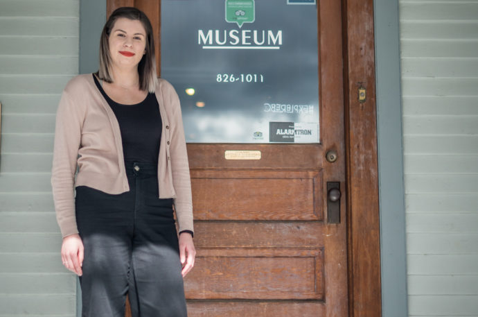 Woman in front of front door that says museum on it