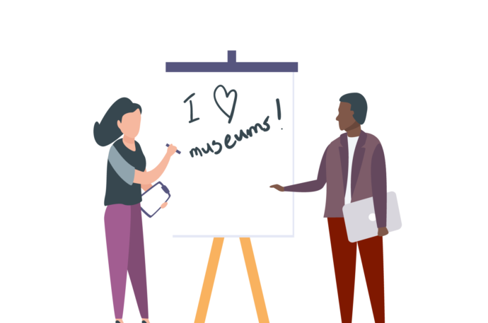 """Two people writing """"I love museums"""" on a flip chart"""